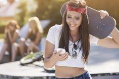 Mujer joven en skatepark con sus amigos Imagen de archivo