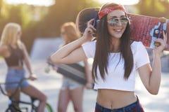 Mujer joven en skatepark con sus amigos Foto de archivo