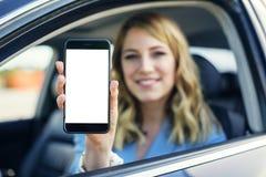 Mujer joven en smartphone de los salones del automóvil con la pantalla en blanco imagenes de archivo