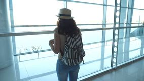 Mujer joven en sombrero con la mochila que se coloca en el terminal del aeropuerto y que mira la ventana Muchacha que espera su a almacen de metraje de vídeo