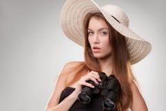 Mujer joven en sombrero con los prismáticos Fotografía de archivo libre de regalías