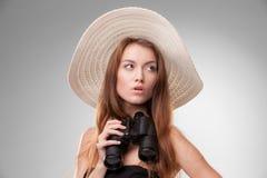 Mujer joven en sombrero con los prismáticos Fotos de archivo libres de regalías