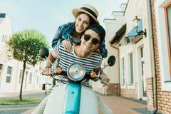 Mujer joven en sombrero de paja y hombre hermoso en los sunglases que montan la vespa junto Imagenes de archivo