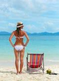 Mujer joven en sombrero que toma el sol en la playa tropical Foto de archivo libre de regalías