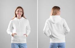 Mujer joven en suéter en blanco de la sudadera con capucha en opiniones ligeras del fondo, delanteras y traseras imágenes de archivo libres de regalías