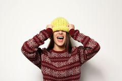 Mujer joven en suéter caliente y sombrero hecho punto en el fondo blanco imagenes de archivo