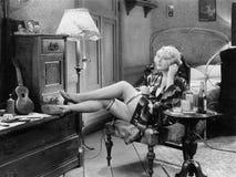 Mujer joven en su dormitorio que se sienta en una silla con sus piernas en un aparador y una tabla con algunas botellas de alcoho Foto de archivo libre de regalías