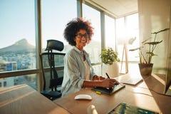 Mujer joven en su lugar de trabajo creativo foto de archivo
