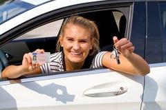 Mujer joven en su nuevo coche Foto de archivo libre de regalías