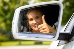 Mujer joven en su nuevo coche con el pulgar para arriba Imagenes de archivo
