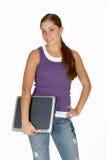 Mujer joven en tapa del tanque púrpura con la computadora portátil bajo el brazo Foto de archivo