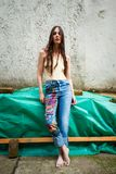 Mujer joven en tejanos del estilo del boho con usos coloridos Imagenes de archivo