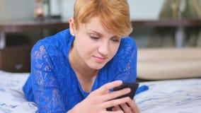 Mujer joven en teléfono azul del uso del vestido en la cama almacen de metraje de vídeo