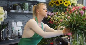Mujer joven en tienda floral almacen de video