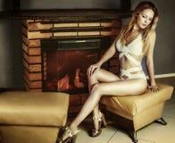 Mujer joven en traje de baño en los talones que se sientan cerca de la chimenea Fotografía de archivo