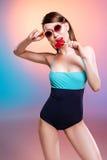 Mujer joven en traje de baño y gafas de sol que come el caramelo en forma de corazón Imágenes de archivo libres de regalías
