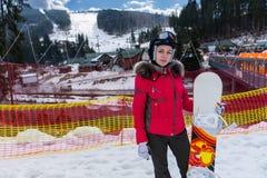 Mujer joven en traje de esquí, casco y las gafas del esquí que se colocan con sn Fotos de archivo libres de regalías