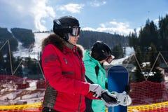 Mujer joven en traje de esquí, con el casco y las gafas del esquí poniendo Fotografía de archivo