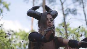 Mujer joven en trajes de teatro del diablo o del baile maléfico en funcionamiento de la demostración del bosque o ritual de la fa almacen de video