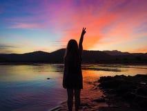 Mujer joven en un amanecer hermoso Fotos de archivo