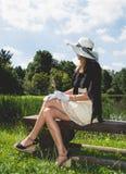 Mujer joven en un banco de madera fotos de archivo libres de regalías