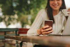Mujer joven en un café usando el teléfono móvil Fotos de archivo libres de regalías