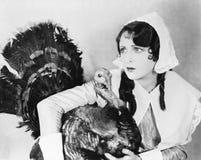 Mujer joven en un capo que abraza un pavo (todas las personas representadas no son vivas más largo y ningún estado existe Th de l fotografía de archivo libre de regalías