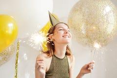 Mujer joven en un casquillo celebrador que engaña alrededor en un partido en el fondo del globo imagenes de archivo