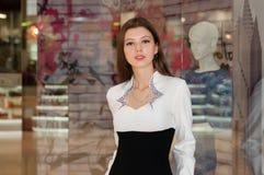 Mujer joven en un centro comercial en el fondo de las ventanas de la tienda Imágenes de archivo libres de regalías