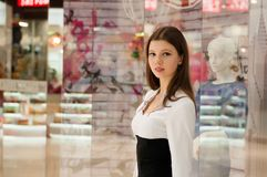 Mujer joven en un centro comercial en el fondo de las ventanas de la tienda Fotos de archivo