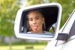 Mujer joven en un coche que pega la lengua hacia fuera Fotografía de archivo libre de regalías