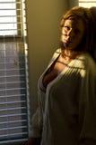 Mujer joven en un cuarto oscuro Foto de archivo
