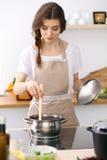Mujer joven en un delantal punteado del biege que cocina la sopa en la cocina fotos de archivo libres de regalías
