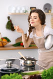 Mujer joven en un delantal punteado del biege que cocina la sopa en la cocina fotografía de archivo