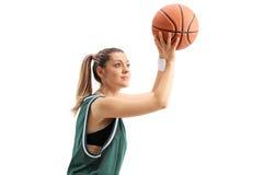 Mujer joven en un jersey verde que lanza un baloncesto Fotografía de archivo
