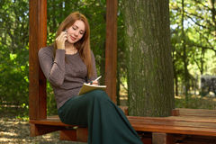 Mujer joven en un parque que habla en el teléfono Foto de archivo libre de regalías