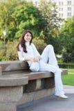 Mujer joven en un parque que parece sideway Fotos de archivo