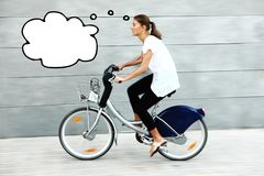 Mujer joven en un pensamiento de la bici Foto de archivo