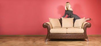 Mujer joven en un sofá foto de archivo