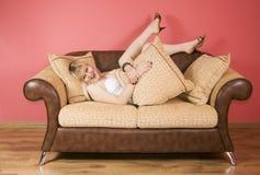 Mujer joven en un sofá fotos de archivo
