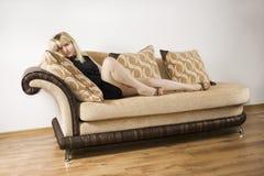 Mujer joven en un sofá fotografía de archivo