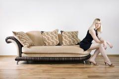 Mujer joven en un sofá imagenes de archivo