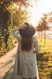Mujer joven en un sombrero con el retrato al aire libre de la taza terma del termo en luz del día soleada suave Otoño Puesta del  fotos de archivo
