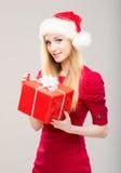 Mujer joven en un sombrero de la Navidad que lleva a cabo un presente Foto de archivo