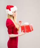 Mujer joven en un sombrero de la Navidad que lleva a cabo un presente Fotos de archivo libres de regalías