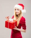Mujer joven en un sombrero de la Navidad que lleva a cabo un presente Foto de archivo libre de regalías