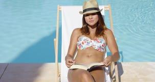 Mujer joven en un sombrero de moda que se relaja en el sol almacen de metraje de vídeo