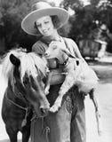 Mujer joven en un sombrero de vaquero que sostiene una cabra mientras que se inclina contra su potro (todas las personas represen Imagen de archivo libre de regalías