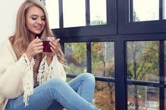 Mujer joven en un suéter por la ventana fotos de archivo