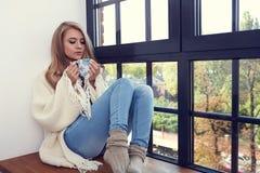 Mujer joven en un suéter por la ventana fotografía de archivo libre de regalías